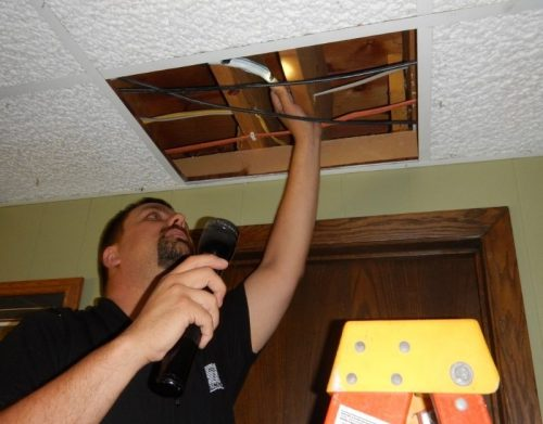 Home inspector inspecting above a ceiling panel